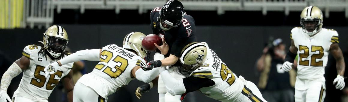 New Orleans Saints players Marshon Lattimore and Marcus Davenport force a fumble by Atlanta Falcons QB Matt Ryan.